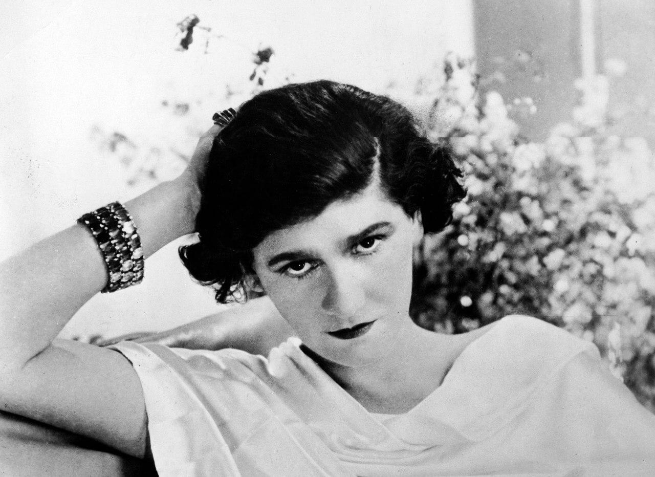 Siyah beyaz çekilmiş resim Coco Chanel ,arka planda flu çiçekler.
