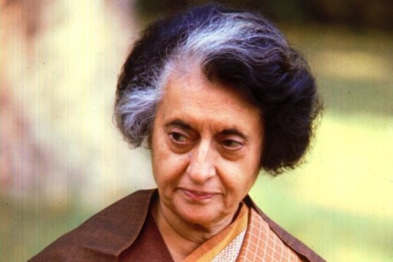 Arka planı flu ağaçlar beraberin tarite iz bırakan kadın İndira Gandhi.