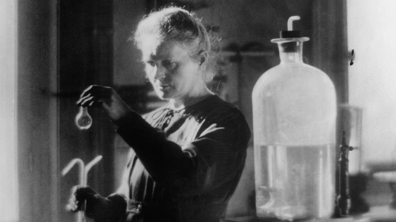 Deney tüpleri elinde olan siyak beyaz bir çekim ile serum bulunan Maria Curie.