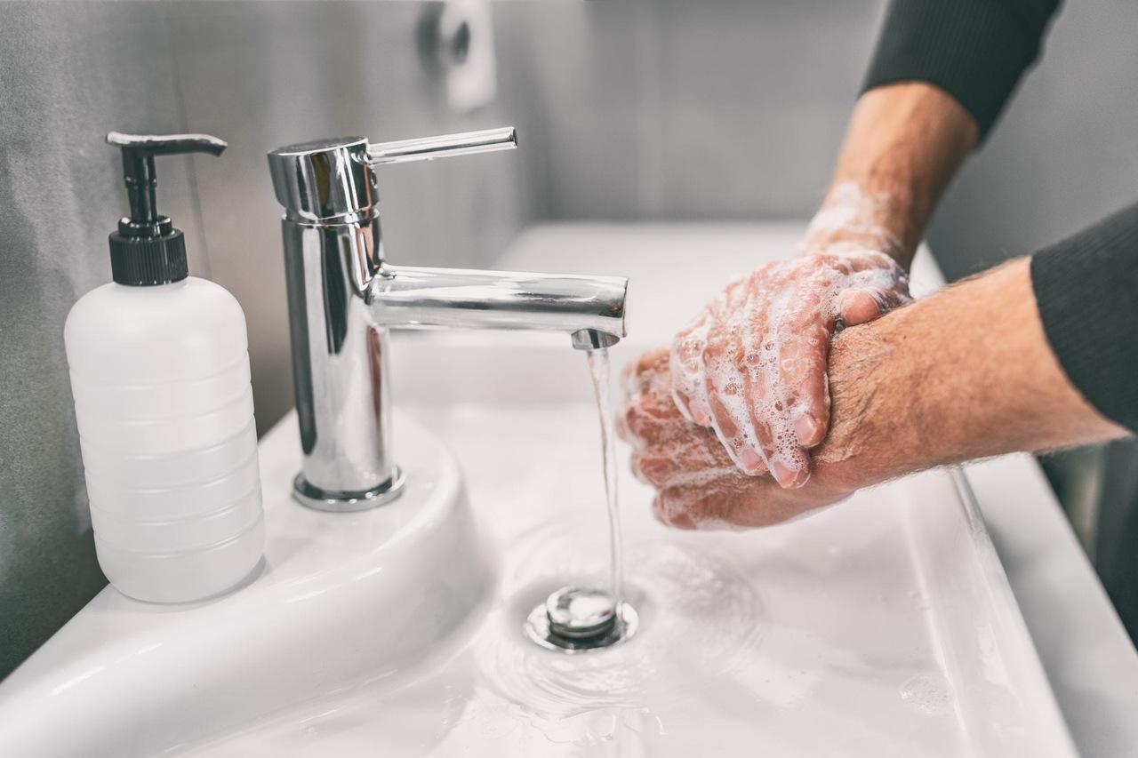 lavaboda sabunla ellerini yıkayan kişi