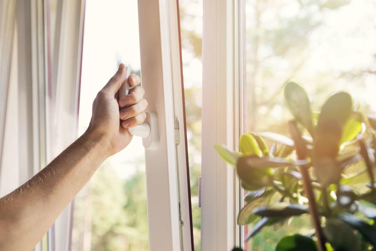 Evi havalandırmak için pencereyi açan el