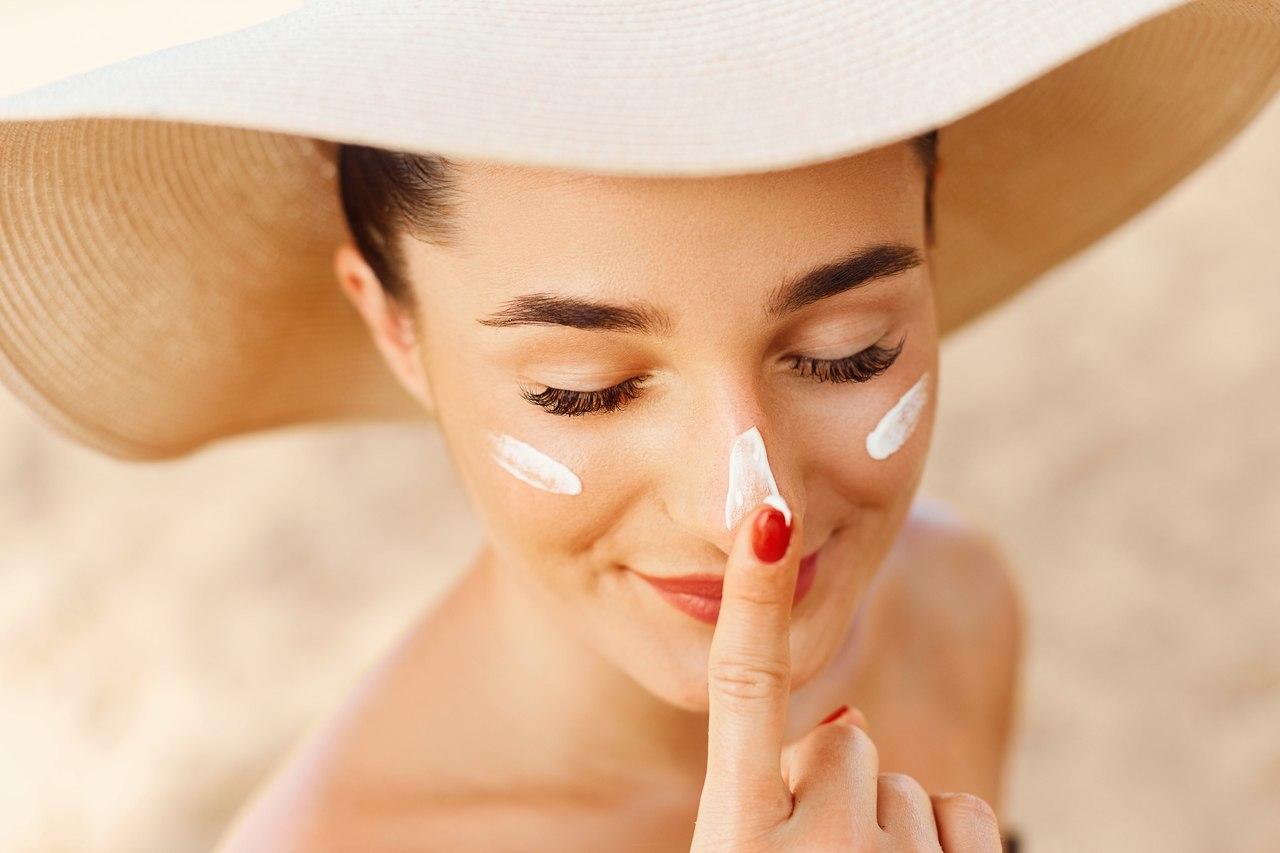 Yüzüne güneş kremi süren şapkalı kadın
