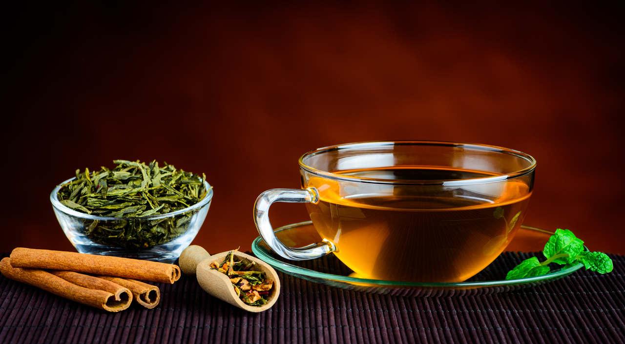 yanında yeşil çay yaprakları bulunan ve cam bardakta servis edilen yeşil çay