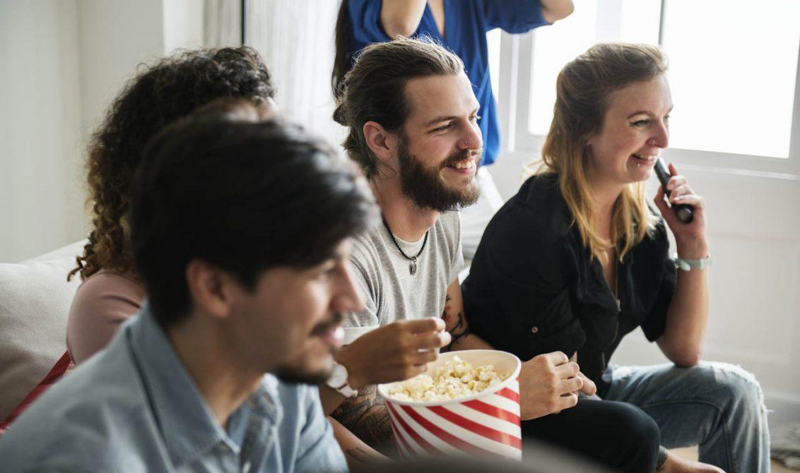 Kanepede oturan ve film izleyen bir grup arkadaş