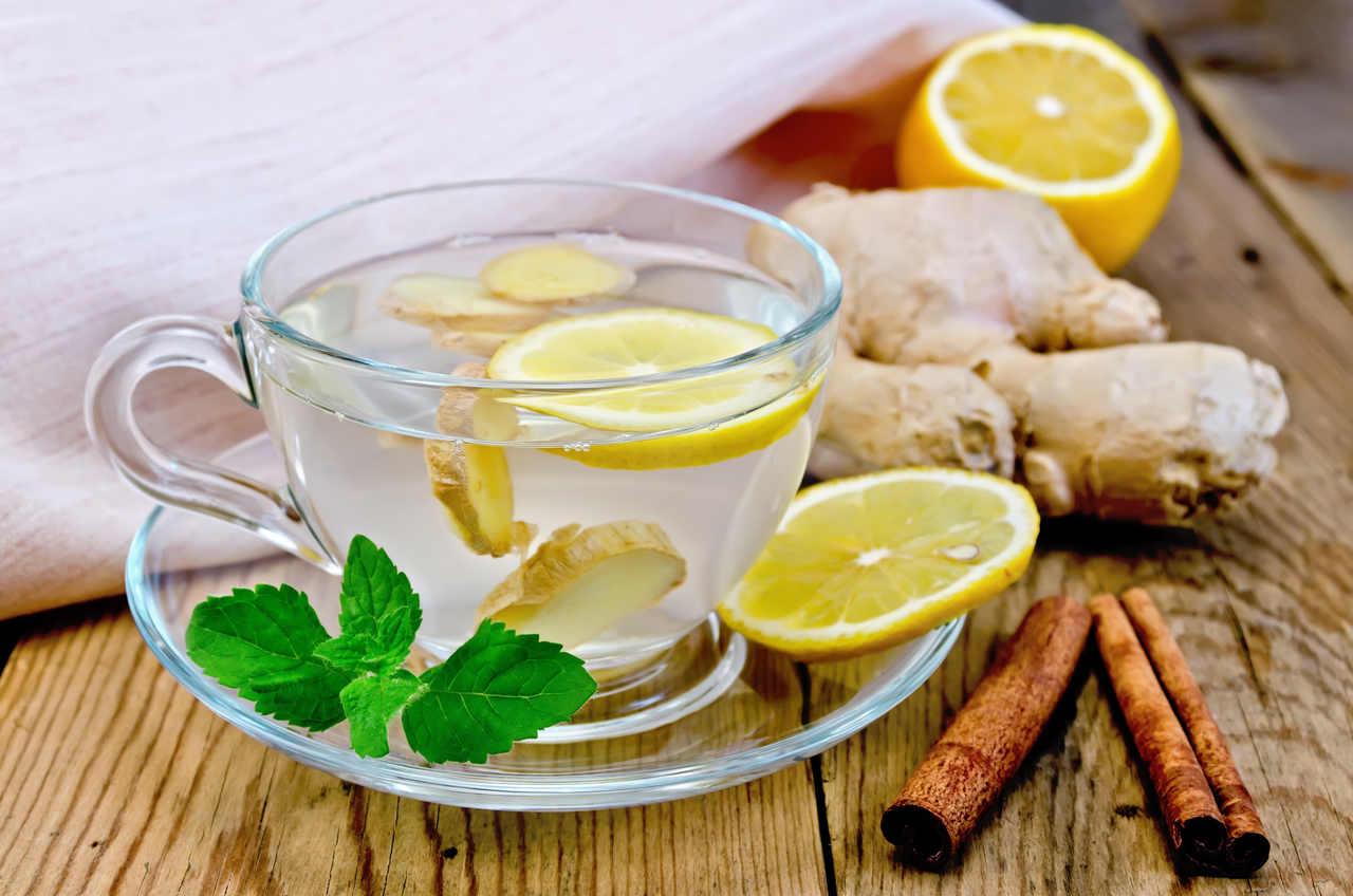 içerisinde limon dilimi ile servis edilen ve yanında taze zencefil ile çubuk tarçın bulunan zencefil çayı görseli