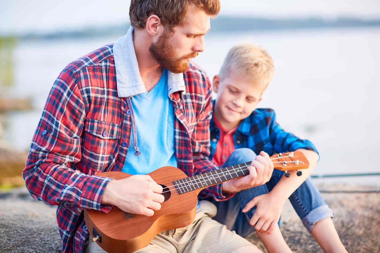 oğluyla birlikte ukulele çalan bir baba