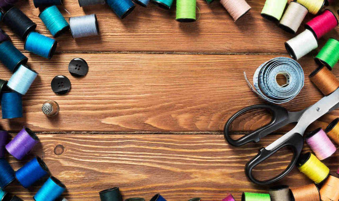 ahşap bir masa üzerinde rengarenk ipler ve makas