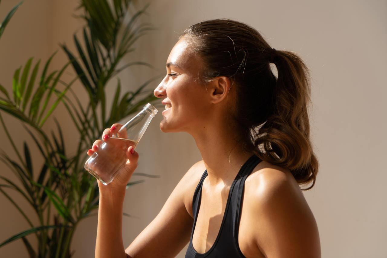 gülümseyerek su içen genç bir kadın