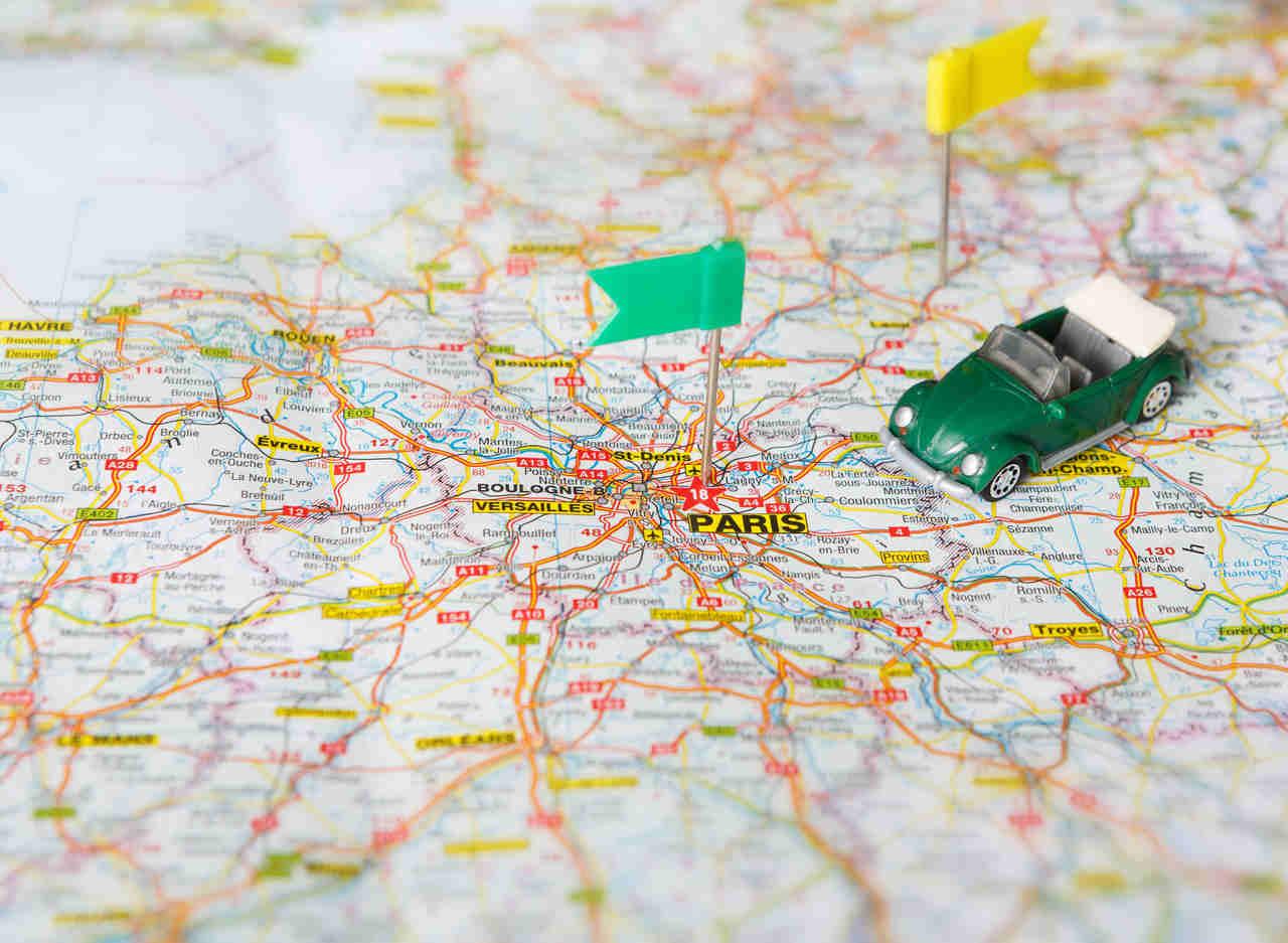 harita üzerinde bir oyuncak araba ve paris üzerinde mini bayrak
