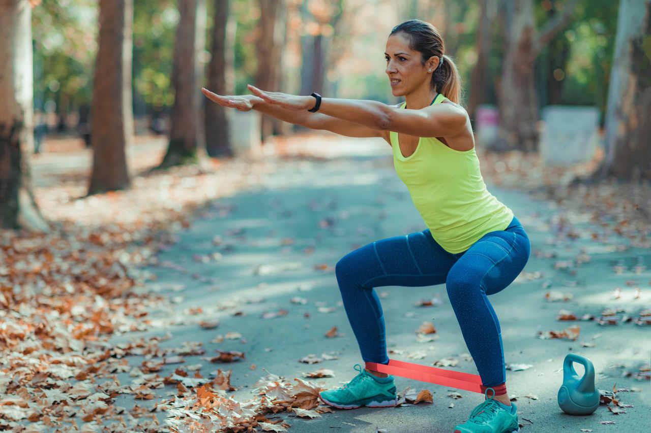 Ormanda spor yaparken direnç bandı kullanan kadın