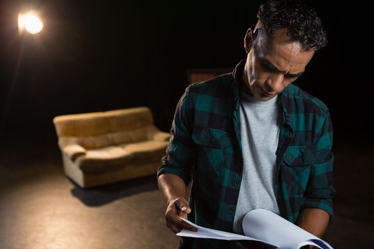 Sahnede oyun metni okuyan bir aktör