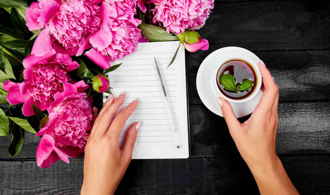 Bir masanın üzerinde duran ve yanında pembe çiçekler ve bir fincan cay bulunan deftere not tutan kadın görseli