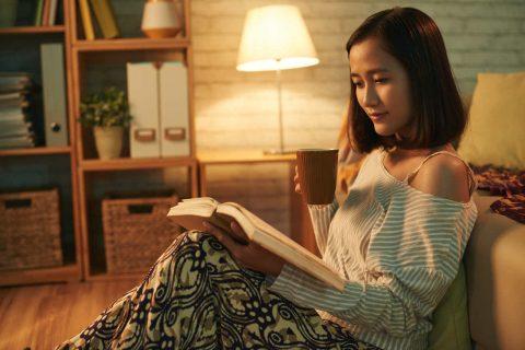 Koltukta oturup kitap okuyan genç bir kadın
