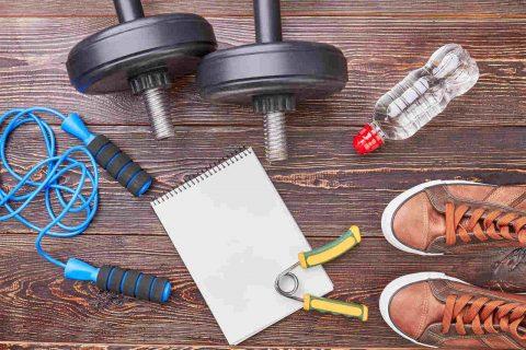 Spor ayakkabı, dumbell, atlama ipi, su ve beyaz kağıt bir arada